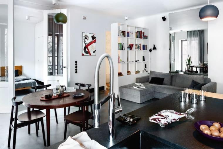 W strefie relaksu kanapa (NAP). Duński stół kupiony na Allegro otaczają inspirowane starymi wzorami krzesła (Fameg). Na ścianie plakat 'Bauhaus' - urodzinowy prezent od przyjaciół. Oświetlenie jest ultrafunkcjonalne - trzy proste lampy (Frandsen) i kilkanaście 'oczek' zintegrowanych z sufitem.