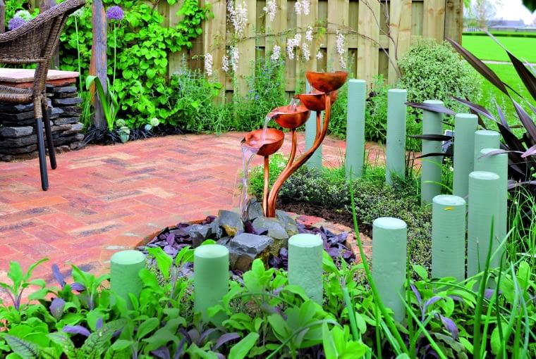 Pastelowa palisadka z betonu oddziela kącik do wypoczynku od reszty ogrodu.