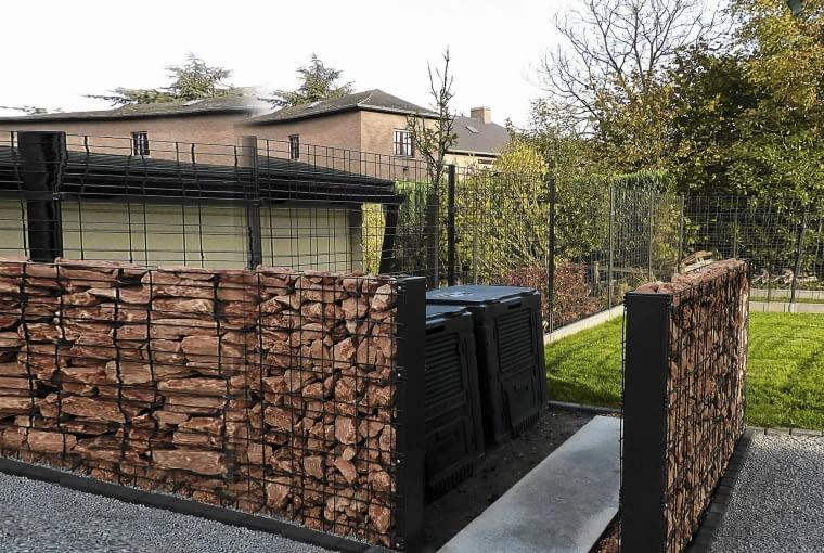 Lite Ścianki z wypełnionych kamieniami drucianych koszy sprawiają, że niezbyt efektowny kącik do kompostowania jest prawie niewidoczny.
