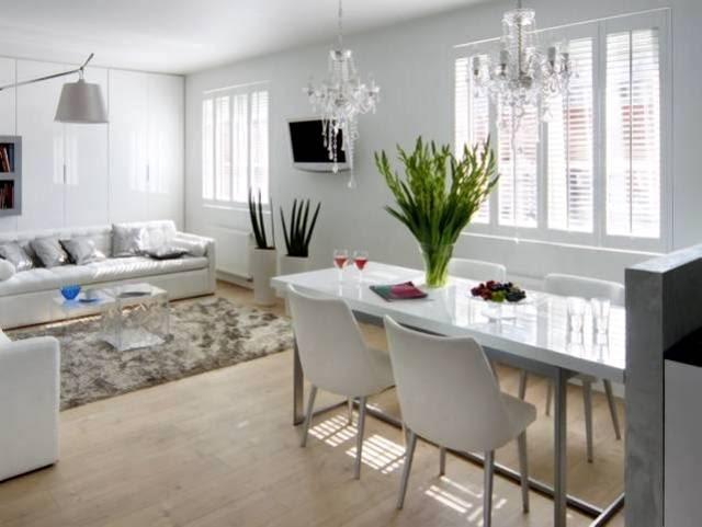 KUCHNIA: Cała w bieli. Elegancki aneks kuchenny idealnie harmonizuje z wystrojem całego wnętrza urządzonego w nowoczesnym stylu. Jedyną wyrazistą ozdobą są tu dwa kryształowe żyrandole.