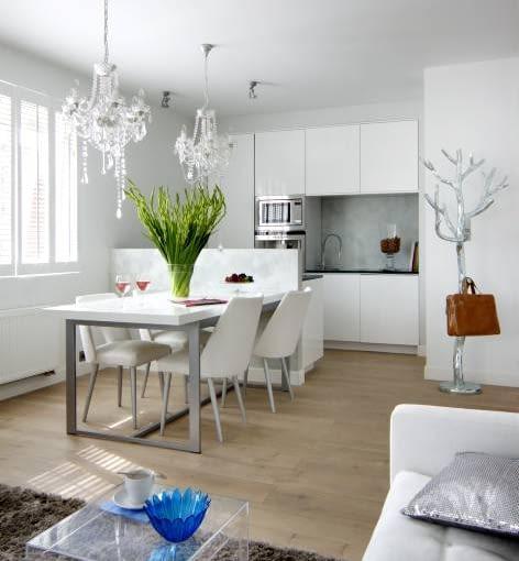Elegancki aneks kuchenny idealnie harmonizuje z wystrojem całego wnętrza urządzonego w nowoczesnym stylu. Jedyną wyrazistą ozdobą są tu dwa kryształowe żyrandole.