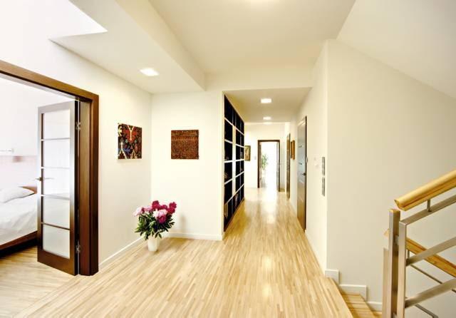 Przestrzeń komunikacyjna na piętrze. Na wprost - wejście do części seniorów, po prawej - fragment klatki schodowej. Na podłodze i na schodach - jesionowy parkiet przemysłowy
