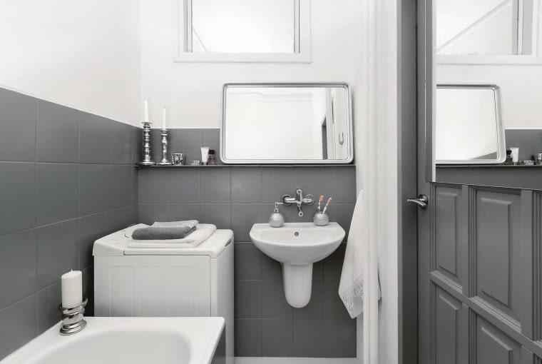 PO ZMIANIE. Płytki na ścianach i na obudowie wanny pomalowano na ciemnoszary kolor, a górną część ścian, po zaszpachlowaniu ubytków - na biały (farbą do wilgotnych pomieszczeń). Inną barwę mają również niektóre dodatki, m.in. rama lustra i dozownik mydła, które odnowiono srebrną farbą w spreju.