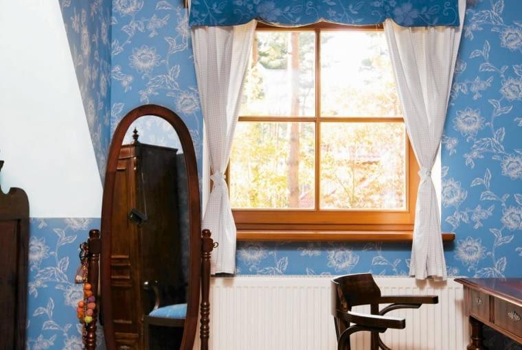 METAMORFOZA SYPIALNI. Wzór na tapecie idealnie pasuje do kwiatowego motywu na lambrekinie. Zasłonki są te same co poprzednio, tyle że upięto je klamrami w kształcie liścia - w ten sposób okno zyskało prawdziwie romantyczną oprawę.