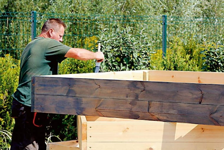 2. Mąż zabezpiecza deski ekologicznym środkiem ochronnym. Od wewnątrz skrzyni przymocowuje do nich zszywkami plastikową taśmę lub membranę kubełkową, by izolowała drewno od wilgotnej ziemi.