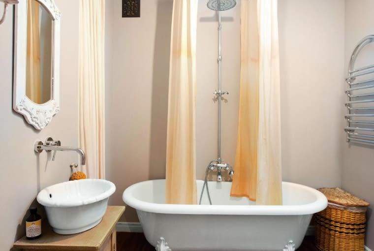 WANNA NA LWICH NÓŻKACH to model Lukrecja (firma Balexim). Okrągły drążek na zasłonę prysznicową (ze sklepu adah.pl) zamocowano w ścianie za pomocą kołków rozporowych. Aby zasłona, zrobiona z tkaniny wodoodpornej, nie rozchylała się w czasie kąpieli, dół jest obciążony ołowianą nitką.