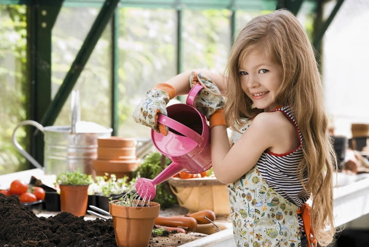 SLOWA KLUCZOWE: child greenhouse growing seeds watering watering can gardening Garden Smiling holding flowerpot cress Standing Caucasian Enjoying Female outdoors Lifestyle One Person Smile Three Quarter Length horizontal potting planting compost portrait happy children girl young girl home grown apron trowel to camera at camera portrait having fun enjoying