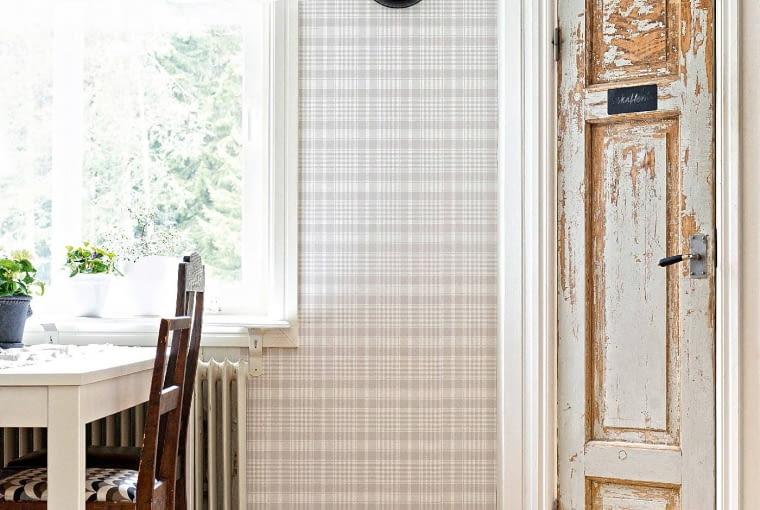 KONTRASTOWO. Ciężkie stare drzwi zestawiono z nową lakierowaną podłogą i tapetą w delikatną kratkę. Dzięki temu nie przytłoczyły wnętrza.