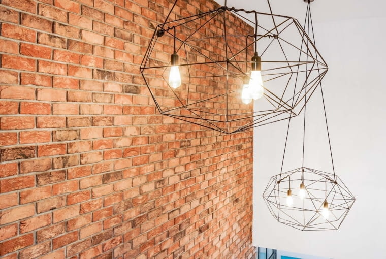 Ceglana ściana, do której przylegają stalowe schody wykończone drewnem, tworzy loftowy klimat, podkreślony jeszcze przez dwie intrygujące, 'pajęcze' lampy z gołymi żarówkami