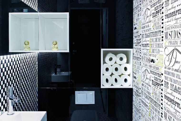 ŚCIANĘ I PODŁOGĘ w toalecie odważnie wykończono mozaiką w szachownicę (mosaic-eurostone.com). Z jej kolorystyką współgra tapeta w gazetowy wzór. Ścianę z podwieszonym sedesem zabudowano schowkami. Polakierowaną na wysoki połysk czarną powierzchnię ożywiają dwie białe półki-wnęki.