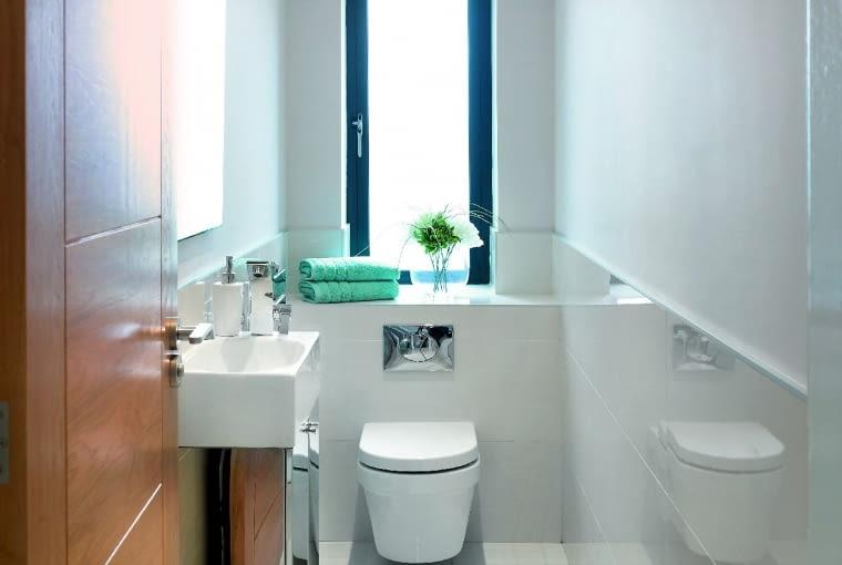 Jak najwięcej światła, naturalnego lub sztucznego. Okno w toalecie to luksus; jeśli go nie ma, zadbajmy o odpowiednie oświetlenie (najlepsze będą lampy emitujące światło o barwie zbliżonej do dziennego, np. ledowe). A do wykończenia toalety użyjmy materiałów odbijających światło (m.in. błyszczących).