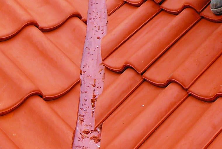 Zbyt krótki i za wąski kosz dachowy jest przyczyną przeciekania dachu. Z boku brakuje też odpowiednio przyciętych dachówek