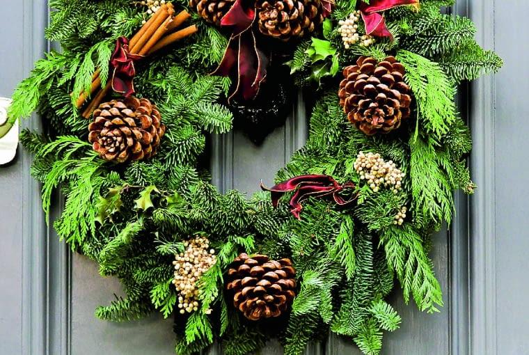 Adwentowy wieniec jest atrakcyjną dekoracją drzwi wejściowych. Zamiast świec lepiej jednak użyć dużych szyszek lub gałązek z owocami, np. róży lub tarniny