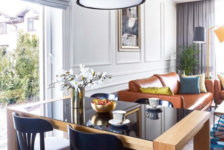 DREWNIANY STÓŁ ma blat z lakierowanej na czarno tafli szkła (Vieri Divani). Świetnie do niego pasują czarne krzesła o tradycyjnej formie z firmy Ton. DOBRY POMYSŁ: mały stół? Pozory. Po rozłożeniu może przy nim usiąść 10 osób. A na co dzień mebel zajmuje niewiele miejsca.