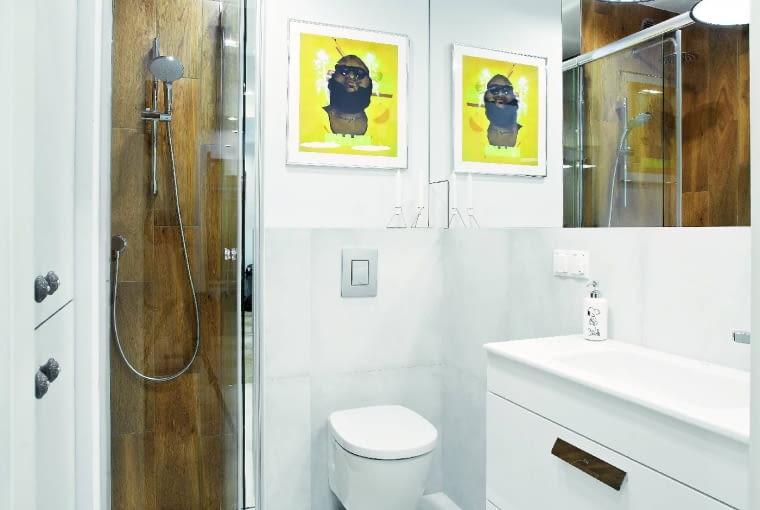 ŁAZIENKĘ zagospodarowano co do centymetra. Przy kabinie prysznicowej udało się zmieścić szafę, wktórej ukryto pralkę, kosz na pranie oraz półki na detergenty, zapas papieru toaletowego itp.