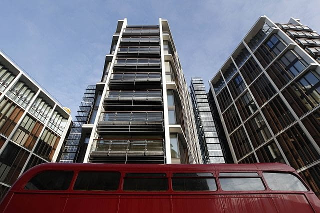 A Routemaster bus passes new development One Hyde Park, in London January 19, 2011. REUTERS/Luke MacGregor (BRITAIN - Tags: BUSINESS)