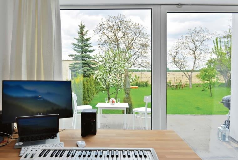Gabinet pana domu ma piękny widok na ogród dzięki ogromnemu oknu tarasowemu, które zajmuje prawie całą ścianę. Jest to główne wyjście z domu na obszerny taras.