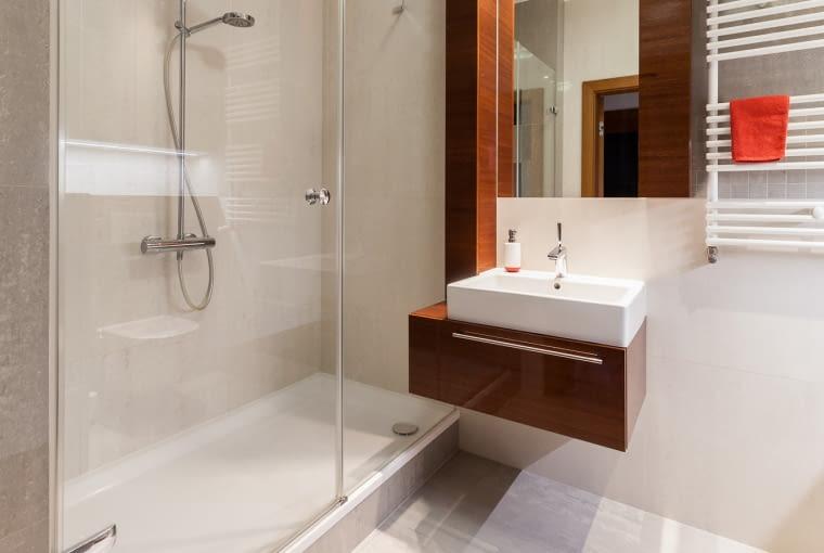W łazience znajduję się duża kabina prysznicowa zamykana szklanymi drzwiami. Zabudowa meblowa nawiązuje stylistycznie do tej w salonie.