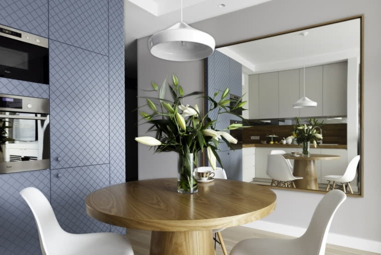 Duże, wiszące lustro sprawia, że mieszkanie wydaje się bardziej przestronne.