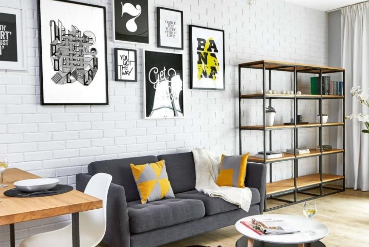 Loftowy charakter wnętrza podkreślają położone na ścianie pokoju dziennego ręcznie cięte płytki klinkierowe (firmy Roben), które projektanci pomalowali na biało. Dobrze koresponduje z nimi beton na przeciwległej ścianie (zdjęcie powyżej). Pokój oświetla lampa 'pająk'. Kable z dekoracyjnymi żarówkami można zawiesić w różnej odległości od punktu centralnego, zmieniając tym samym kształt żyrandola. Podobna lampa wisi nad stołem - dla odmiany uformowana w supeł. Jasne drewno mebli i ciepły odcień podłogowych desek dodały wnętrzu przytulności.
