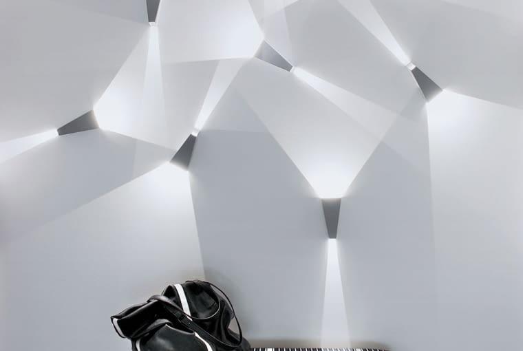 W korytarzu naścienne oprawy Delta Lighting tworzą rzeźbę ze światła (proj. kompozycji J. Szadkowski). Tapicerowana ławeczka ze studio Alberto Pinto.