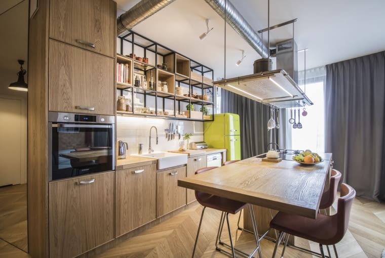 Podobną konstrukcję stworzono w kuchni - tutaj zamiast górnego rzędu szafek znalazły się kubikowe półki.