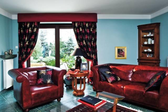Do tego salonu zostały wybrane zasłony, które dzięki mocnej barwie zrównoważyły kolorystykę wnętrza. Zmieniła się jego atmosfera, a wystrój stał się bardziej harmonijny. <BR />DEKORACJE OKIEN - Z LAMBREKINEM. Meble w mocnym czerwonym kolorze nazbyt wyróżniały się na tle ścian i podłogi w odmiennym, chłodnym odcieniu. Tę dysproporcję wyrównały czarne, wzorzyste zasłony i uszyte z tej samej tkaniny poduszki.