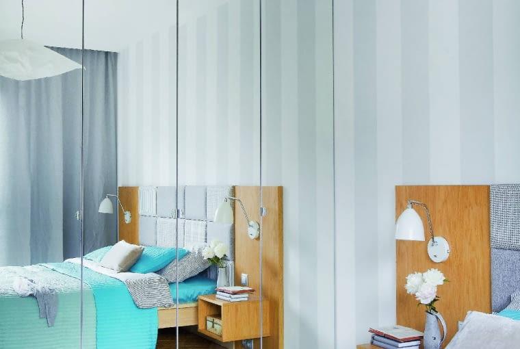 W SYPIALNI na szerokim zagłówku (dobudowanym do łóżka z IKEA) zamontowano podwieszane stoliki nocne. Kinkiety są z Leroy Merlin. Szklane fronty szafy (również z IKEA) optycznie powiększają pokój.