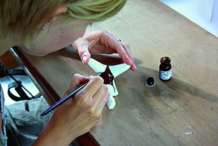 Natalia poświęca dużo czasu na perfekcyjne dopracowanie projektów. Tu: maluje figurki Swimmer i Bikini - złota farba zostanie wypalona w temp. 820oC.