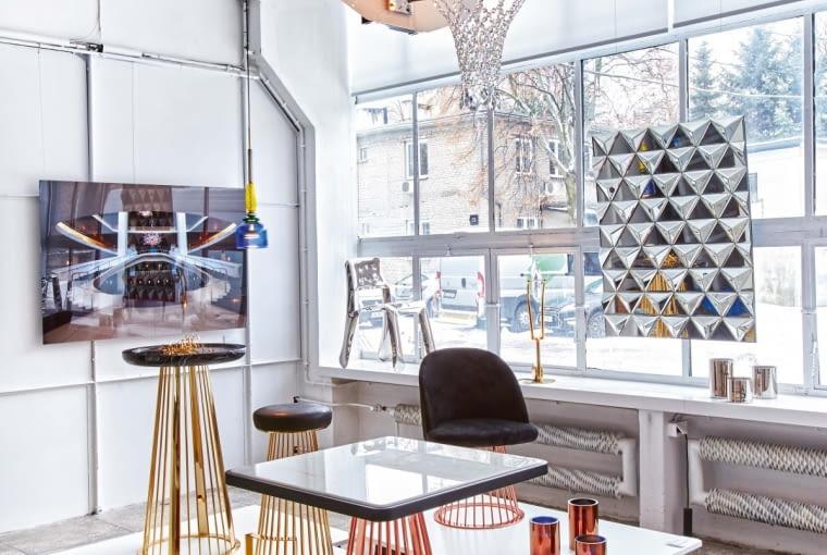 Stoliki i fotel z kolekcji Rendez-vous (Gio Pagani), nad nimi żyrandol Street Ball Lukáša Houdka. Na tle okna kryształowa lustrzana dekoracja Billion square (Reflections Copenhagen); po lewej fotografia wnętrza Metropolitan Opera autorstwa Borisa Kudlicki.