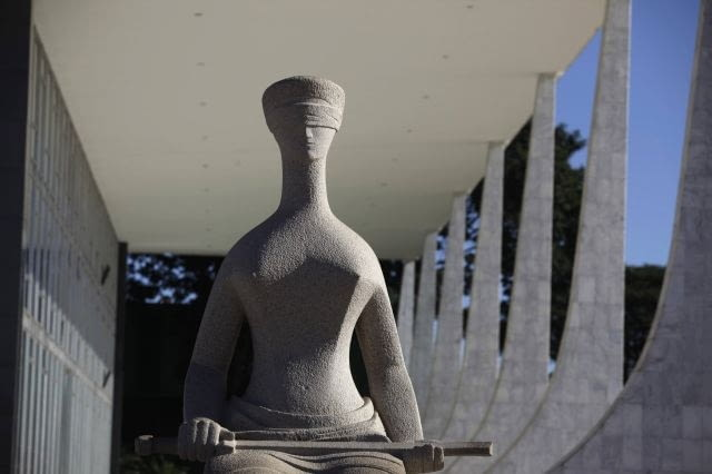 A statue of Justice is seen outside the Brazilian Supreme Court in Brasilia April 7, 2010. The dream was big. In just a few years, Brazil would build a modern capital in the middle of a savanna, an experiment in egalitarianism that would also shift power toward the center of the vast country. As Brasilia turned 50 years old on April 21, 2010, vestiges of that dream live on in Oscar Niemeyer's soaring architecture, the uniform residential apartment blocks, and the plane-like city shape that legend has it was meant to signal the Latin American giant's take-off. Picture taken April 7. To match Feature BRAZIL-BRASILIA/ REUTERS/Ricardo Moraes (BRAZIL - Tags: ANNIVERSARY CITYSCAPE)