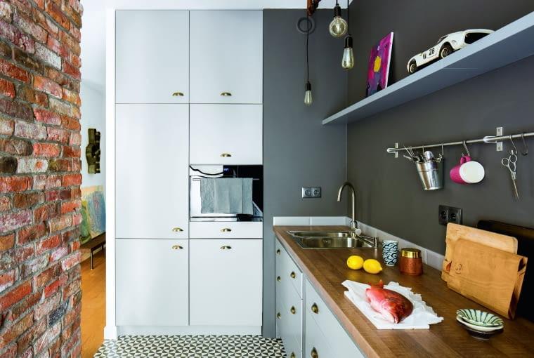 Roboczą strefę kuchni oddziela od salonu ścianka zbudowana z cegły rozbiórkowej. Taki układ pozwala nie przejmować się naczyniami w zlewie.