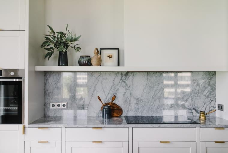 Kuchnia jest prosta i minimalistyczna. Marmur Bardiglio, którym pokryty jest blat i zabezpieczona ściana, stanowi odniesienie do szarości kominka w salonie, zabudowanego w betonowej oprawie.