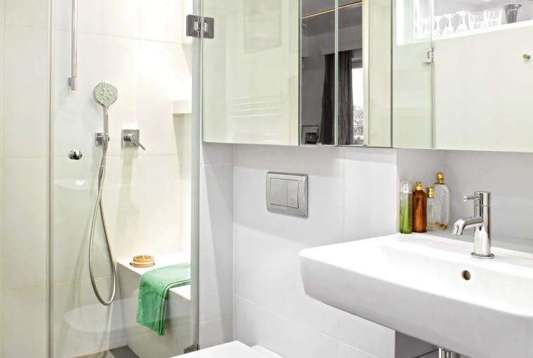 Podłoga w łazience jest taka sama jak w całym mieszkaniu - dębowa. Tylko w kabinie prysznicowej położono płytki gresu. W lustrzanych drzwiach szafki nad umywalką odbija się wybite w ścianie okienko, które doświetla łazienkę od strony kuchni. Siedzisko w kabinie prysznicowej to również praktyczne miejsce na przybory kąpielowe.