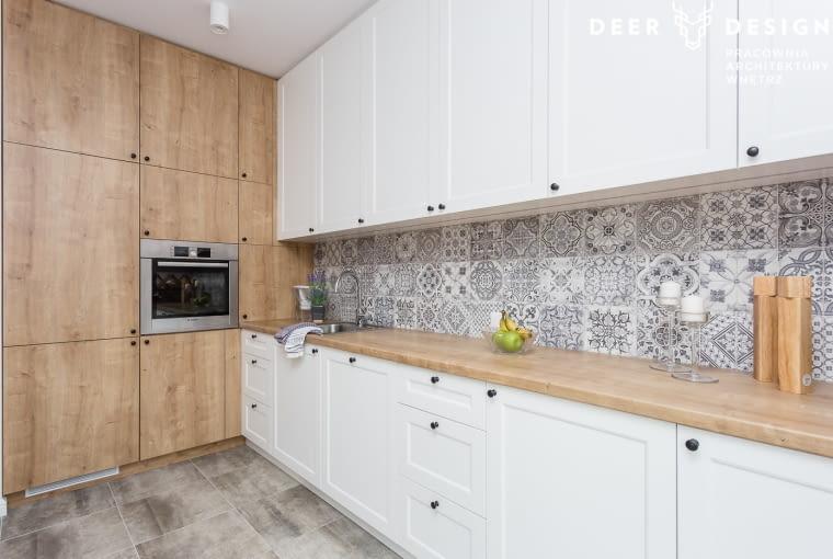 Kuchnię urządzono w bieli z szarymi i drewnianymi akcentami. Układ został zaprojektowany jednorzędowo. Jedna ściana została w całości wykorzystana do przechowywania.