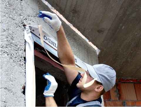 Krok 3. Po wstawieniu ościeżnicy w otwór i zamocowaniu jej kotwami do ściany, od zewnątrz okleja się ją folią paroprzepuszczalną.