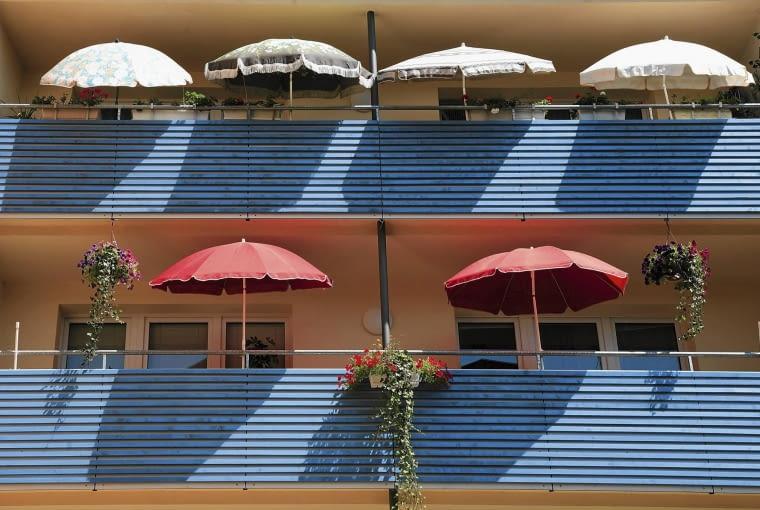 """Na te balkony nie dociera nadmiar słońca dzięki parasolom i osłonom umocowanym do barierek, """"chłodzącym"""" również optycznie - zimnym odcieniem błękitu"""