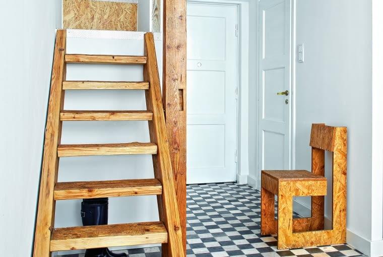 Na ANTRESOLĘ prowadzą solidne drewniane schody. Pod nią zmieściła się szafa. ZPRZEDWOJENNych DRZWI Agnieszka usunęła kilka warstw kolorowej farby ina nowo je pomalowała. Mosiężne okucia wyczyściła zfarby olejnej iwypolerowała pastą Autosol. PODŁOGA wniewielkim przedpokoju została wyłożona płytkami zprzebarwieniami charakterystycznymi dla naturalnego marmuru (sklep industone.pl).