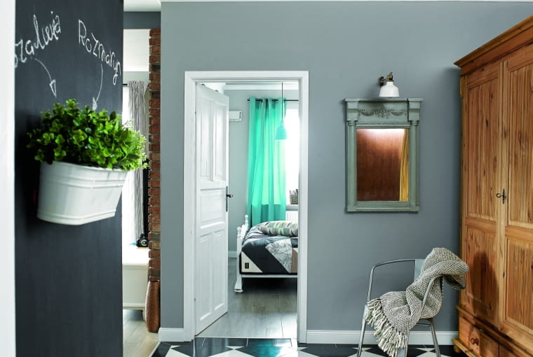 Z PRZEDPOKOJU do części dziennej prowadzi otwarte szerokie wejście. W głębi widać fragment sypialni. Pomalowane na biało łóżko pochodzi, jak kilka innych mebli w mieszkaniu, z targu staroci.