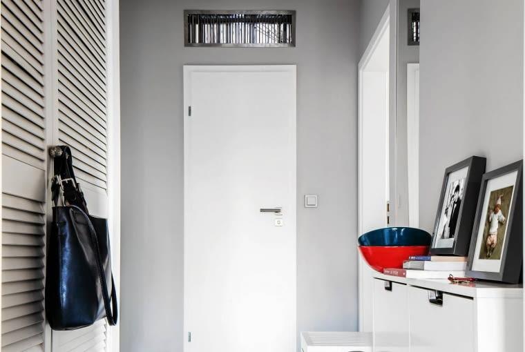W przedpokoju dominuje biel, dzięki czemu pomieszczenie wydaje się większe. Szafy są zamykane żaluzjowymi drzwiami. Do ich formy nawiązuje stołek ze schowkiem pod siedziskiem. Nad drzwiami do łazienki widać dodatkową kratkę wentylacyjną usprawniającą obieg powietrza w tym małym pomieszczeniu.