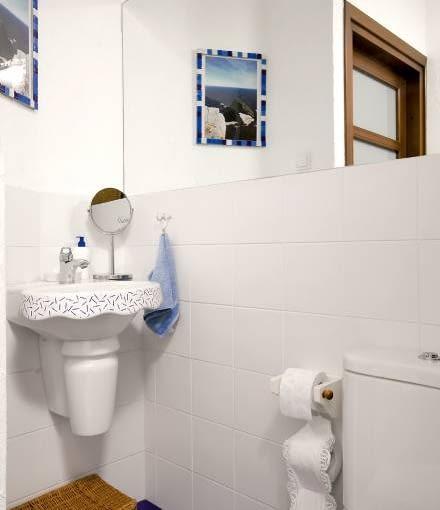 MIESZKANIE. Przyciągające wzrok detale - umywalka z ciekawie ozdobionym frontem i woreczek na papier toaletowy z koronkowym wykoń-czeniem.