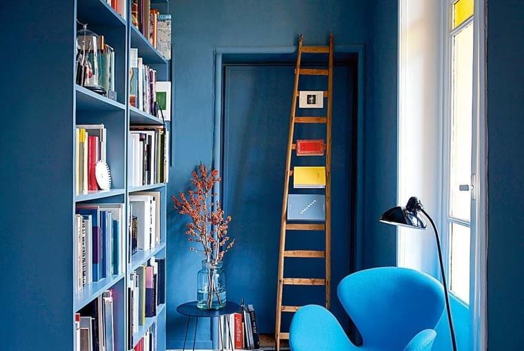 JAK W NIEBIE. Niebieskie ściany, niebieski regał, niebieski fotel. Aby uniknąć efektu pudełka, sufit i okienna wnęka są w odcieni bieli złamanej kroplą błękitu.