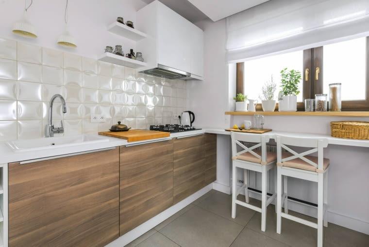 W tej kuchni sprytnie wykorzystano podokienny parapet, który został przedłużony. Ustawiono przy nim jeszcze stołki barowe