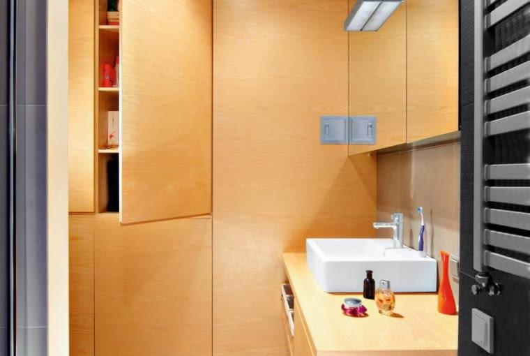 Szafka pod umywalką została zrobiona na wymiar z tego samego materiału co pozostałe schowki - płyty fornirowanej afrykańskim drewnem anegre. Podłoga w tej części pomieszczenia jest z odpornego na wilgoć teku.