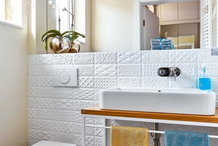 NA ŚCIANĘ w toalecie (i obudowę wanny w łazience) wybrano białe płytki w urozmaicone wypukłe wzory (Vives).
