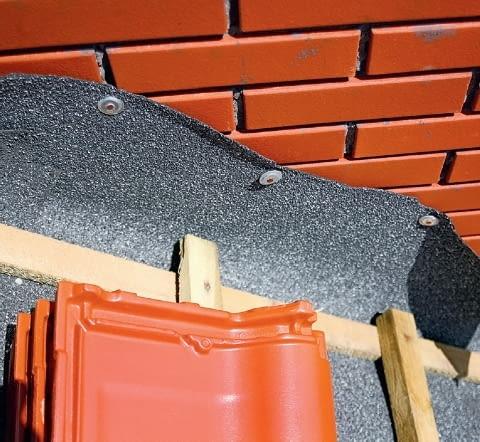 Krok 1. Wystającą nieco ponad łaty folię dachową lub papę wywija się na komin i szczelnie mocuje do niego specjalną taśmą lub papiakami.