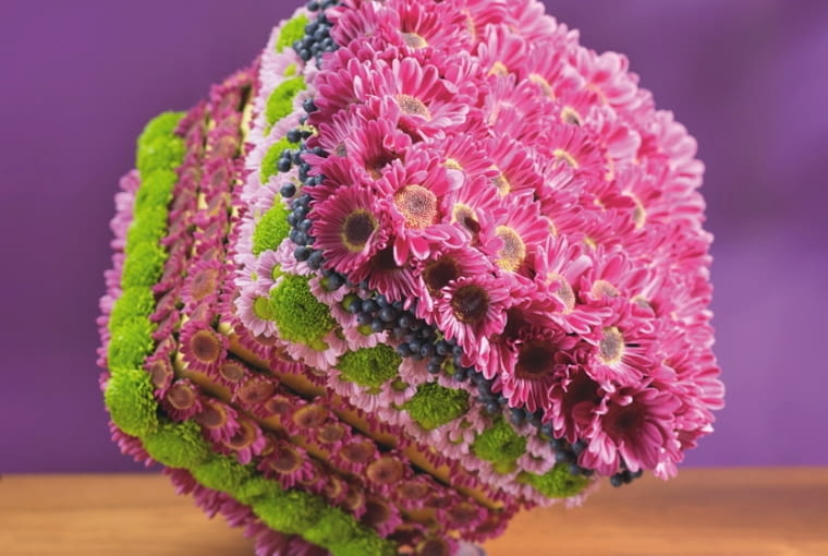 Orientalne kompozycje kwiatowe. Na kubiku z mokrej gąbki florystycznej upięto główki chryzantem gałązkowych i owoce aronii