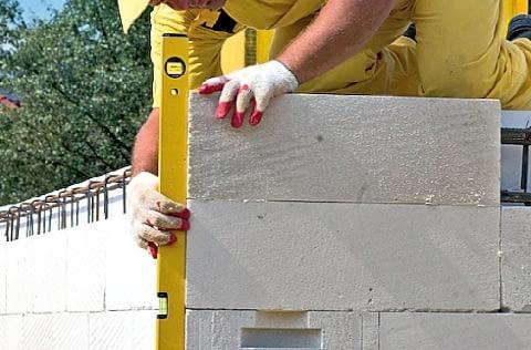 Murowanie zaczyna się od narożników. Elementy układa się tak, by zrównać ich powierzchnię z licem ściany (trzeba wyciąć fragment wełny mineralnej)