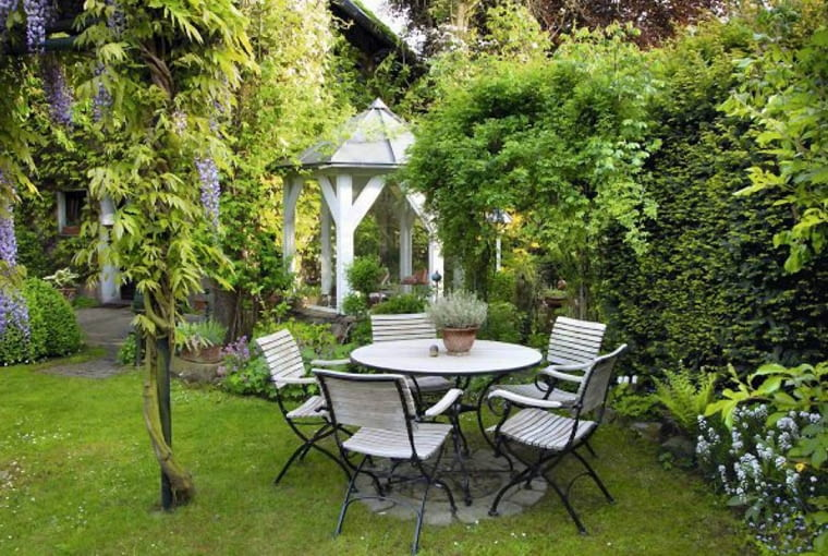 Garden with seating area on lawn, summer house and Wisteria growing over arch