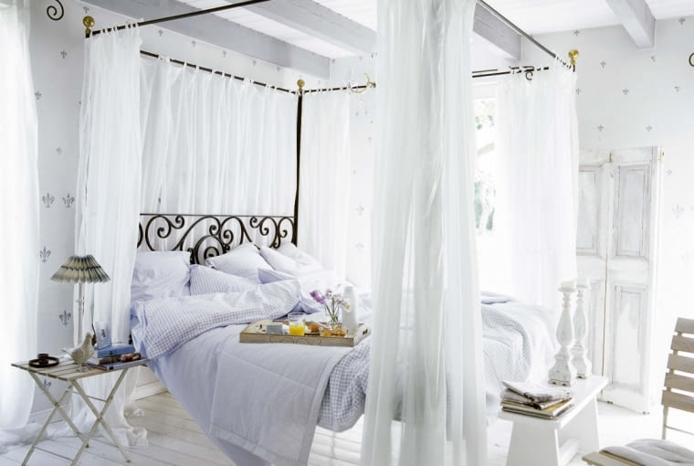 =Country style bedroom with four poster bed and white curtains